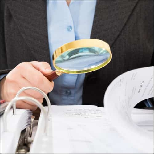 Magnifying glass reviewing documents