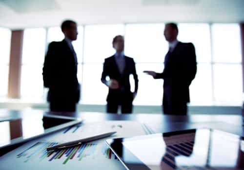 Three business people standing around a table in an office
