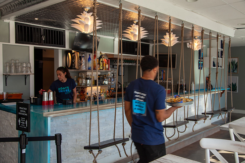 Agave Shore interior, swinging bar stools, server wearing Agave Shore branded shirt