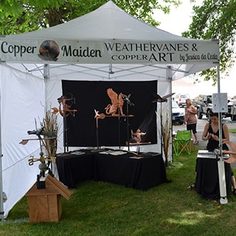 Artist with copper art on display