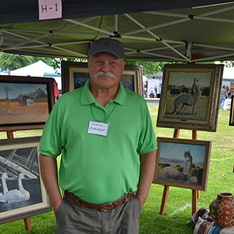 Artist with paintings on display