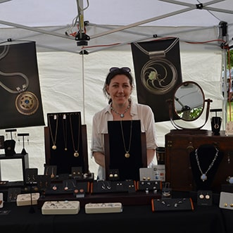 Artist with jewelry on display