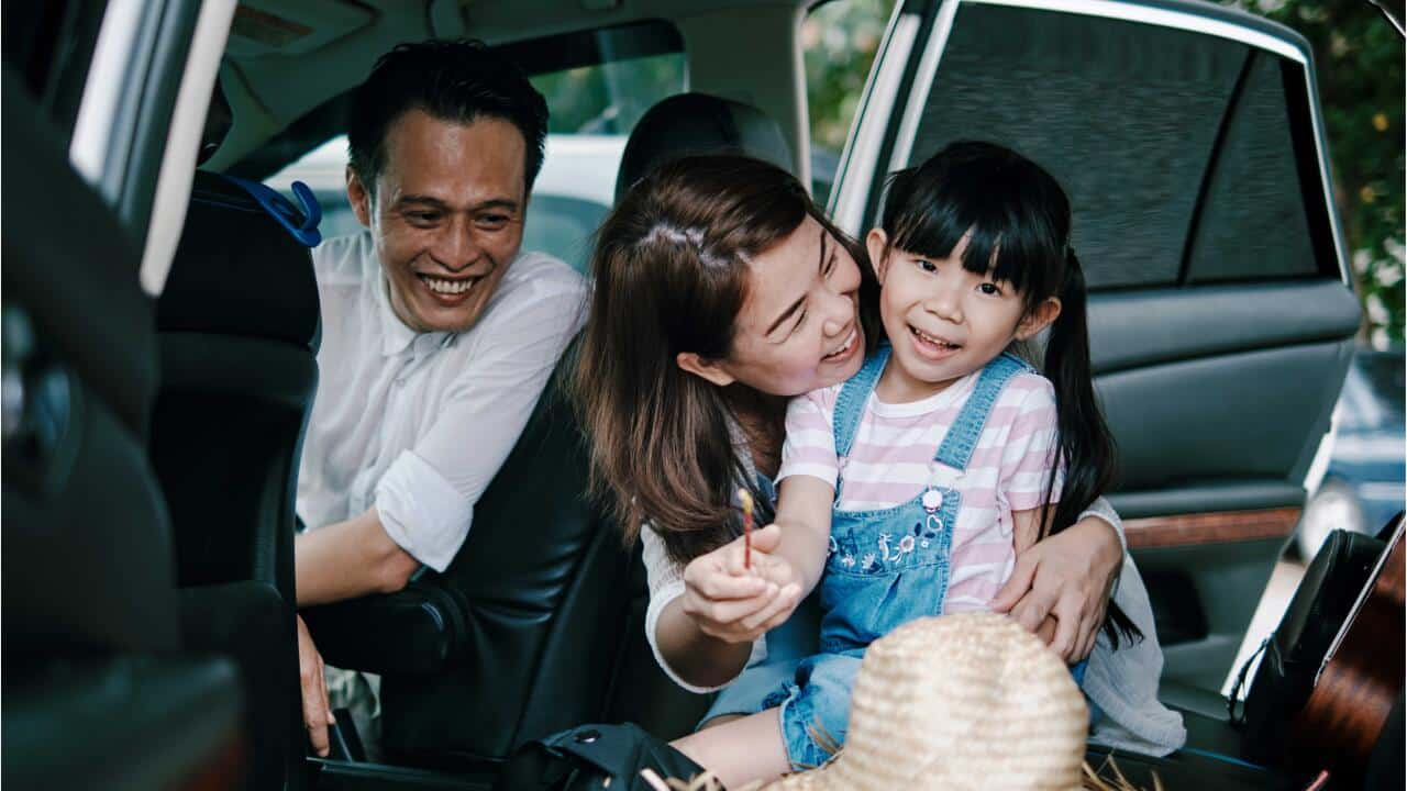 A happy family laughing in their vehicle protected and kept safe by Cartrack's GPS tracking mobility solution.