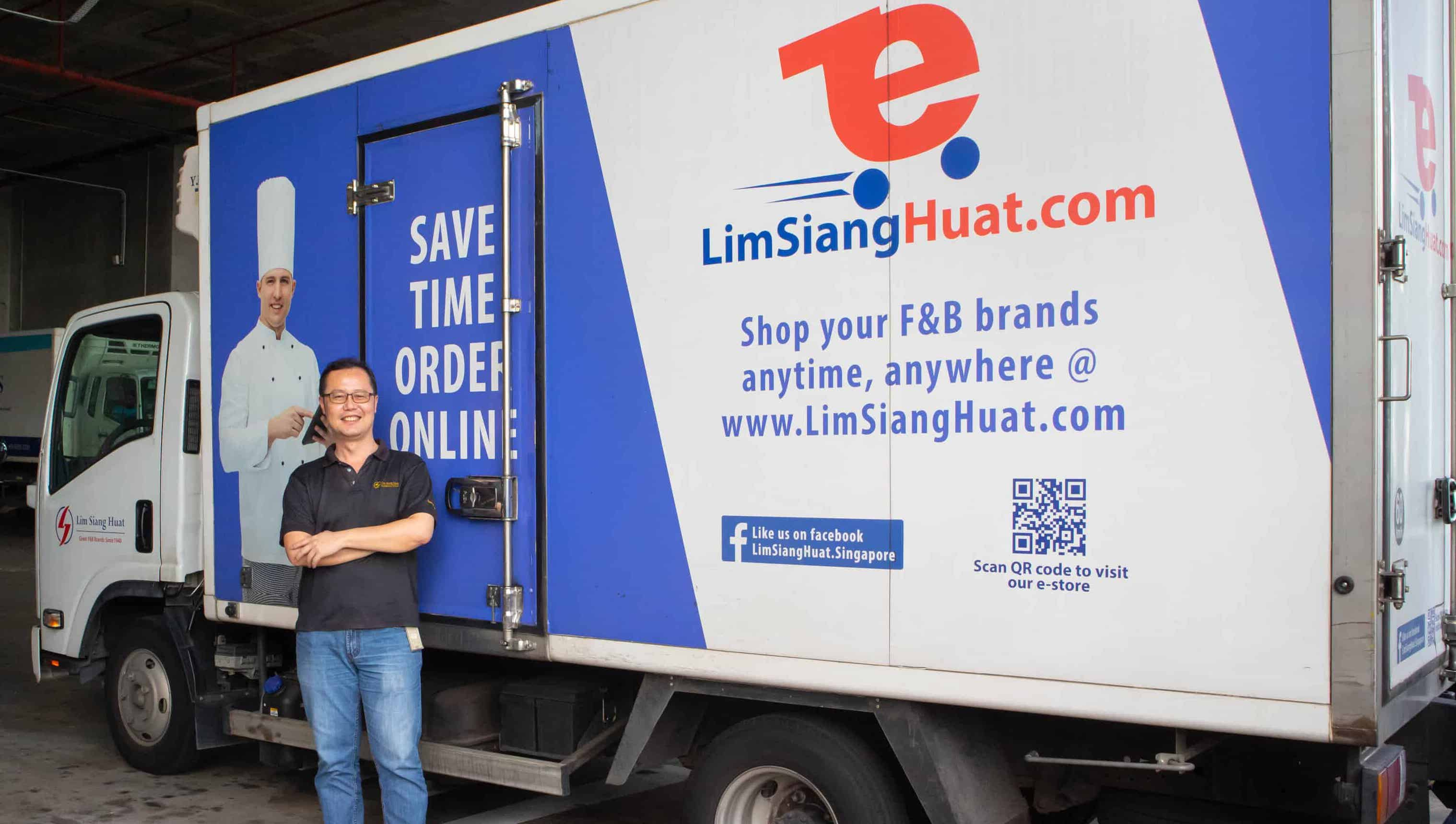 A photo of a Lim Siang Huat's operations manager standing in front of a branded reefer truck that is powered by Cartrack's fleet management solution.