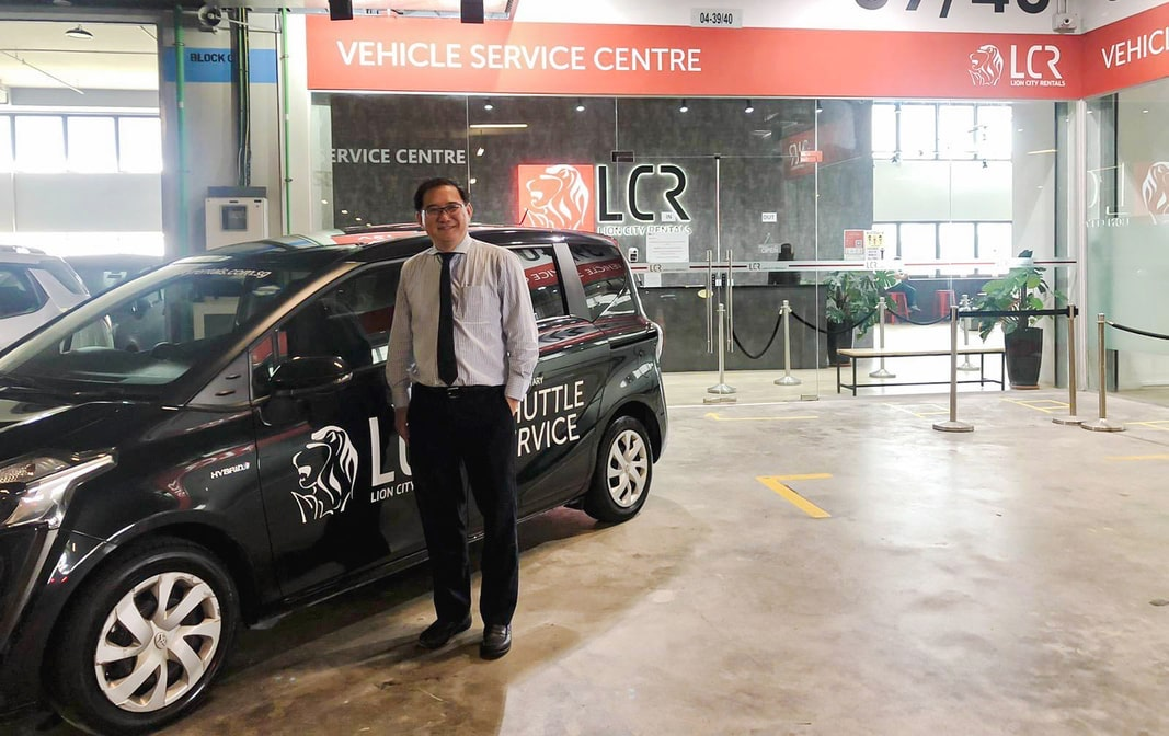 Lion City Rentals management standing in front of a LCR shuttle service vehicle at their vehicle service centre.