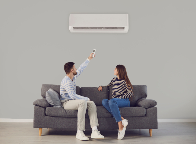 A woman and a man sitting on a couch, the man is turning on the air conditioner with a remote