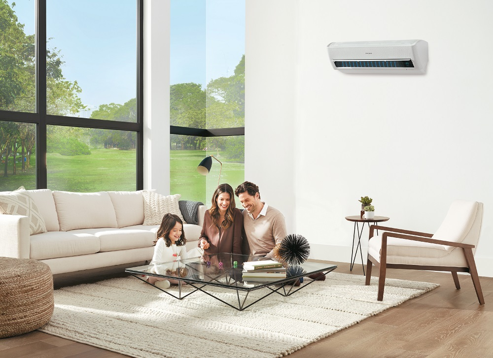 A smiling family sitting on their living room floor, with an air conditioning unit on the wall