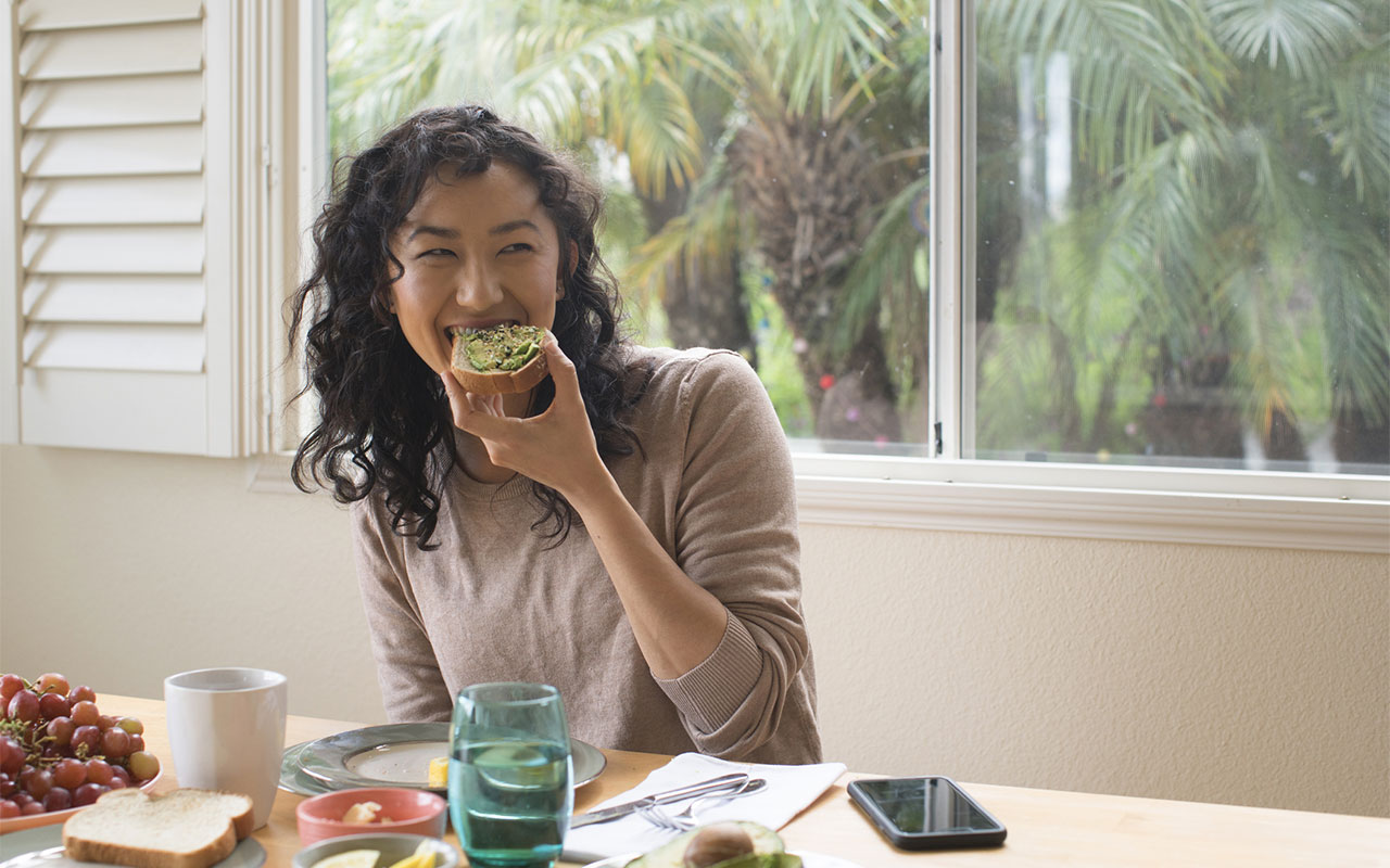 Young woman eating avocado toast at home