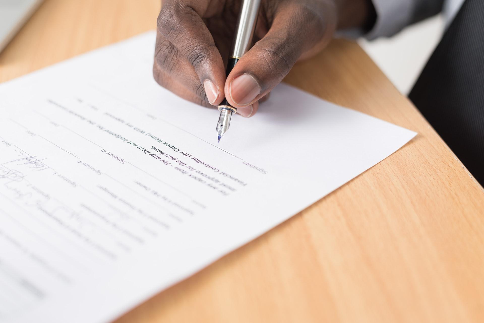 Man håller i en penna och skriver under ett dokument.