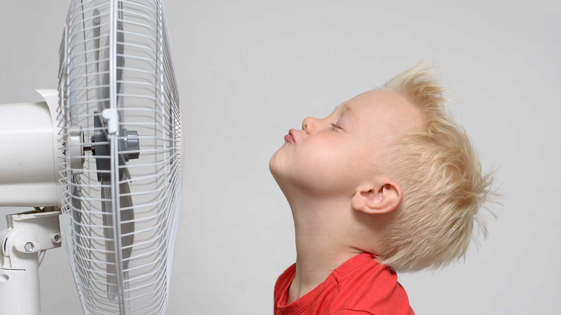 A young boy with his face in fornt of a blowing fan