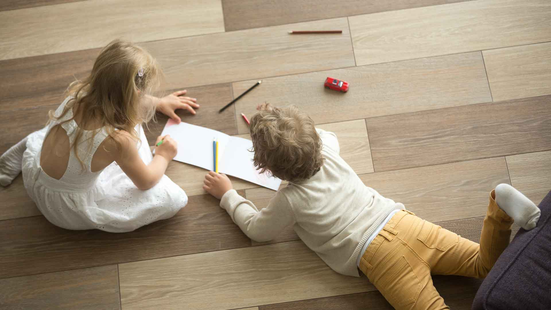 Two children playing contendedly on the floor of a house
