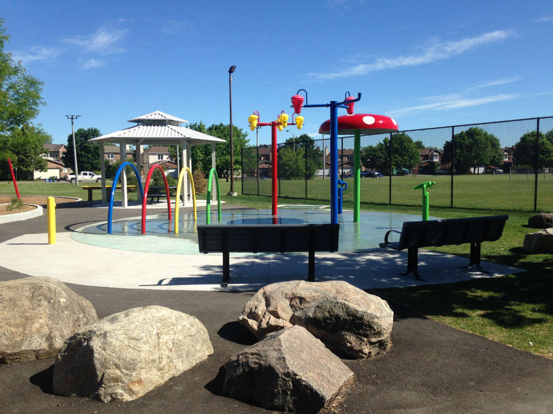 Splashpad play area surrounded by benches in Calzavara Family Park in Ottawa, with a gazebo and grassy field in the background.