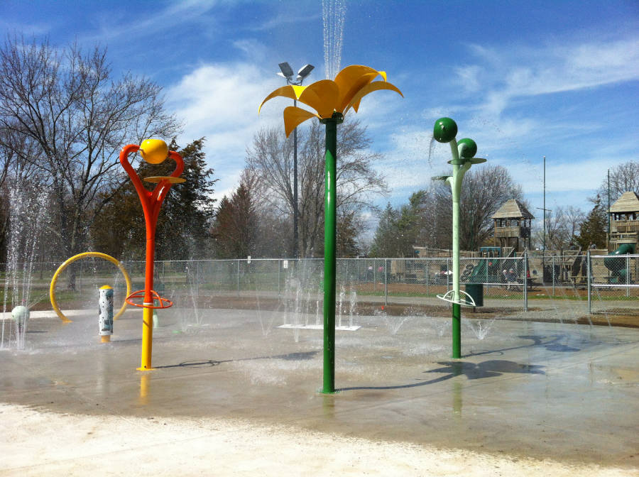 splash pad play area with active fountains in urban park