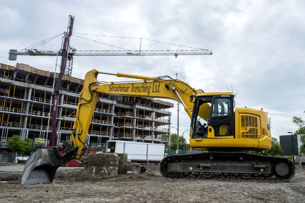 excavator on job site in front of multi-storey building under construction