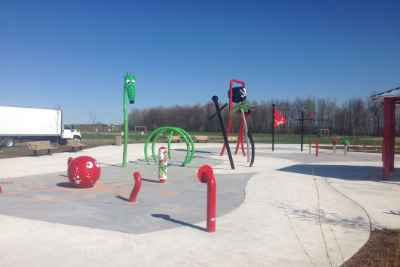 red and green fixtures protruding from concrete splashpad base