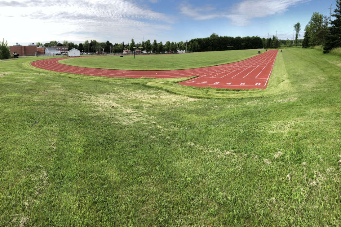 completed red rubber running track in Napanee, Ontario, showing lane numbers