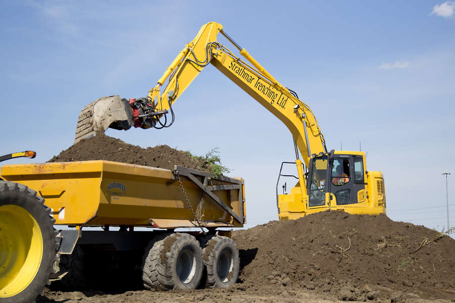 excavator loading an off-road trailer with excavation soil during landscape construction