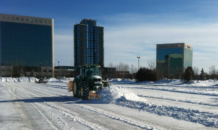 tractor plowing snow in large parking lot in Ottawa