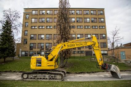 excavator working in front of building