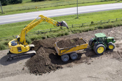 excavator loading soil into offroad trailer