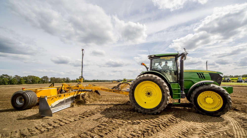 tractor pulling a box blade to level a farm field to improve drainage