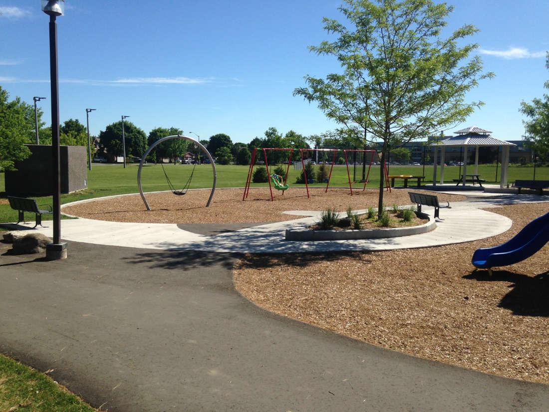 playground in Ottawa's Calzavara Family Park showing swings, slide and walking path