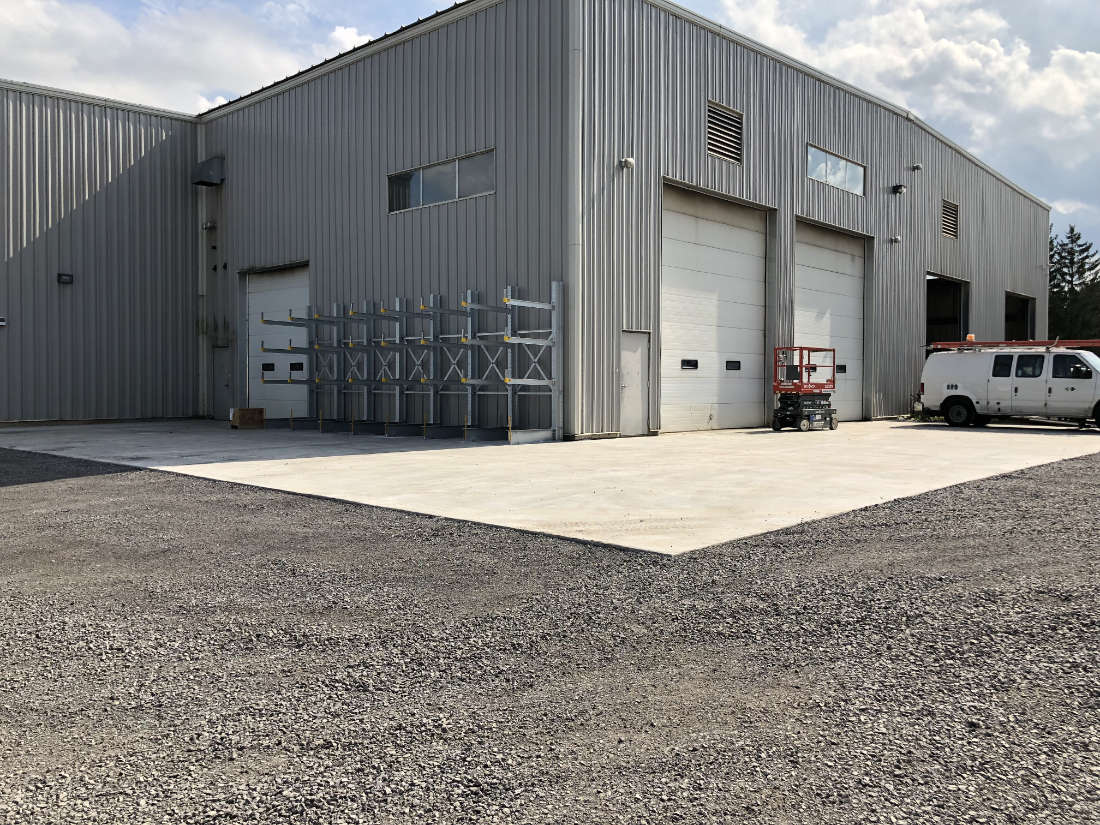 gravel parking lot and concrete loading pads in front of loading doors of industrial building
