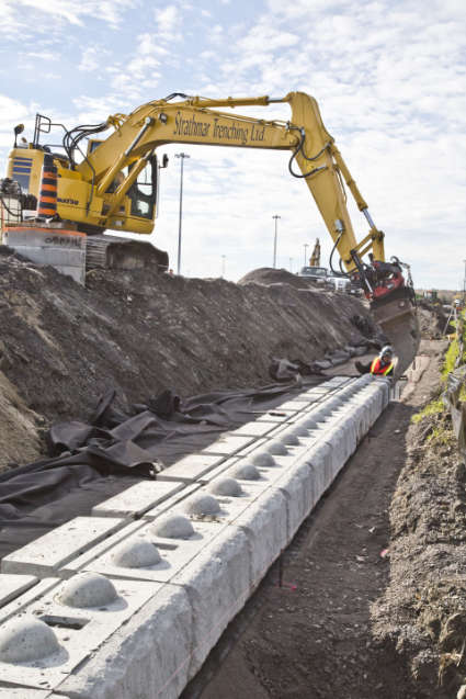 excavator placing sections of concrete retaining wall blocks in place in a trench, with a worker in safety clothing and hardhat ensuring correct placement