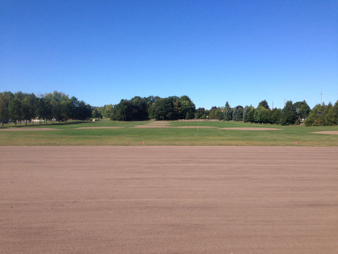 golf course under construction showing driving range area surface prior to paving and target greens