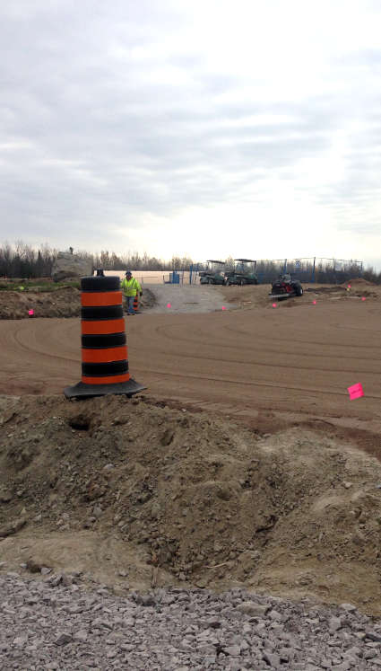 golf course under construction showing graded surface with orange and black safety pylon in foreground