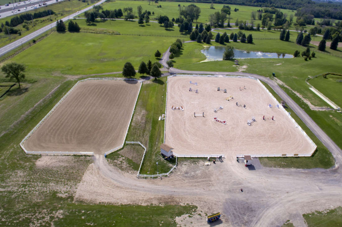 aerial view of horse riding rings at Wesley Clover Parks in Ottawa, with equestrian jump fences set up in one ring
