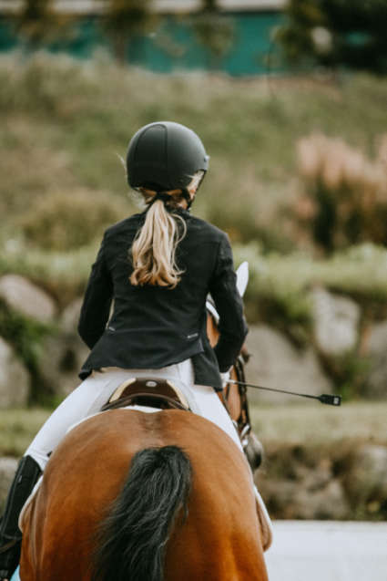 Photo of young rider on a horse viewed from behind by Valerie Fomina on Unsplash