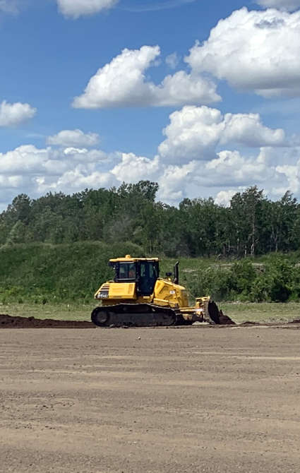 bulldozer working to spread soil to level a field