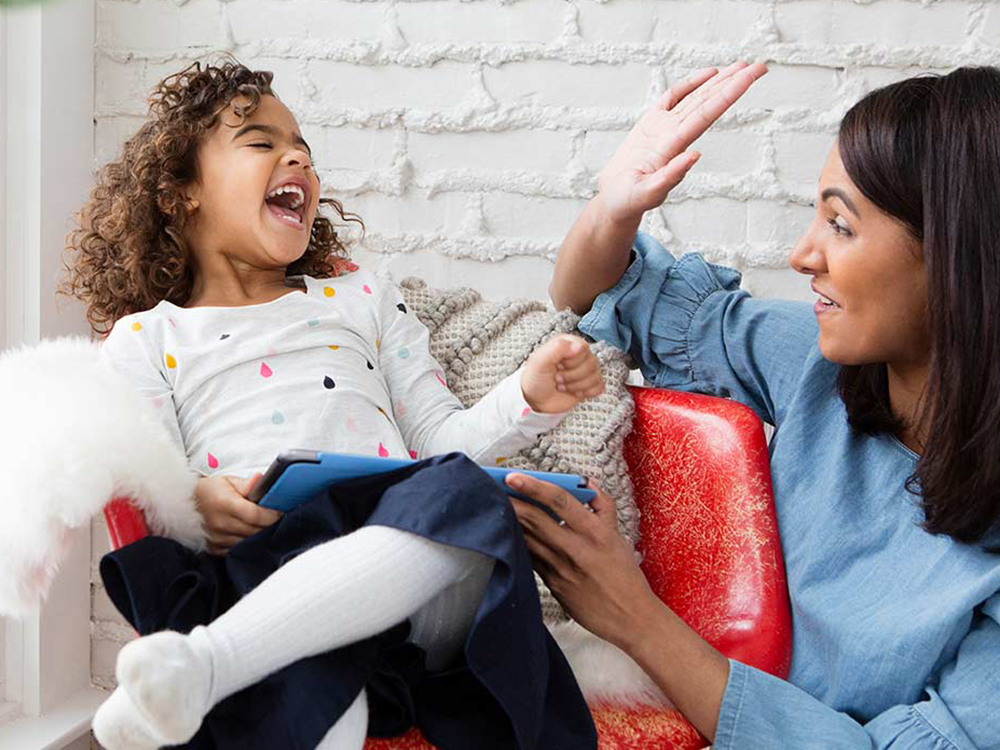 Woman giving a high five to a laughing child