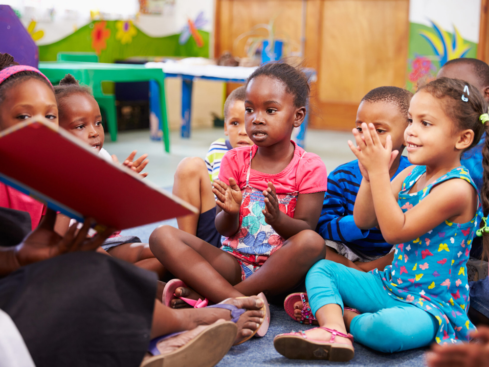 Teacher reading to multiple children as they participate in the activity