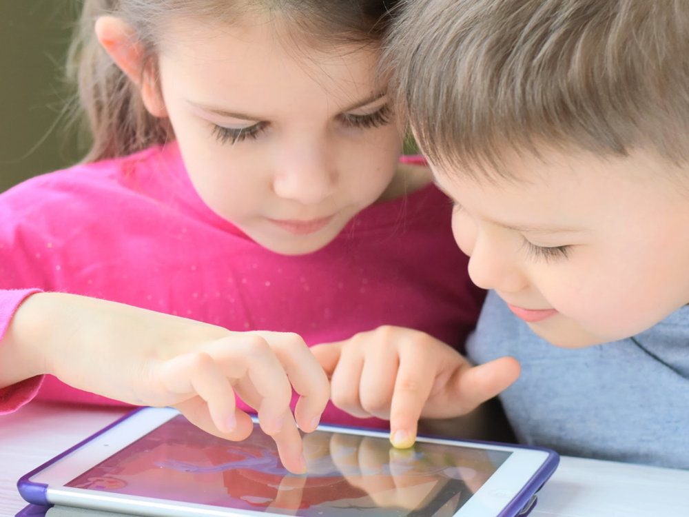 Two children reading from a tablet