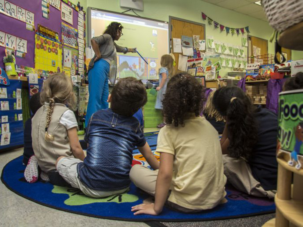 Teacher and child working at the board while the other children give their full attention