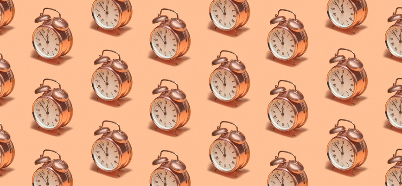 A pattern of alarm clocks on a peach colored background