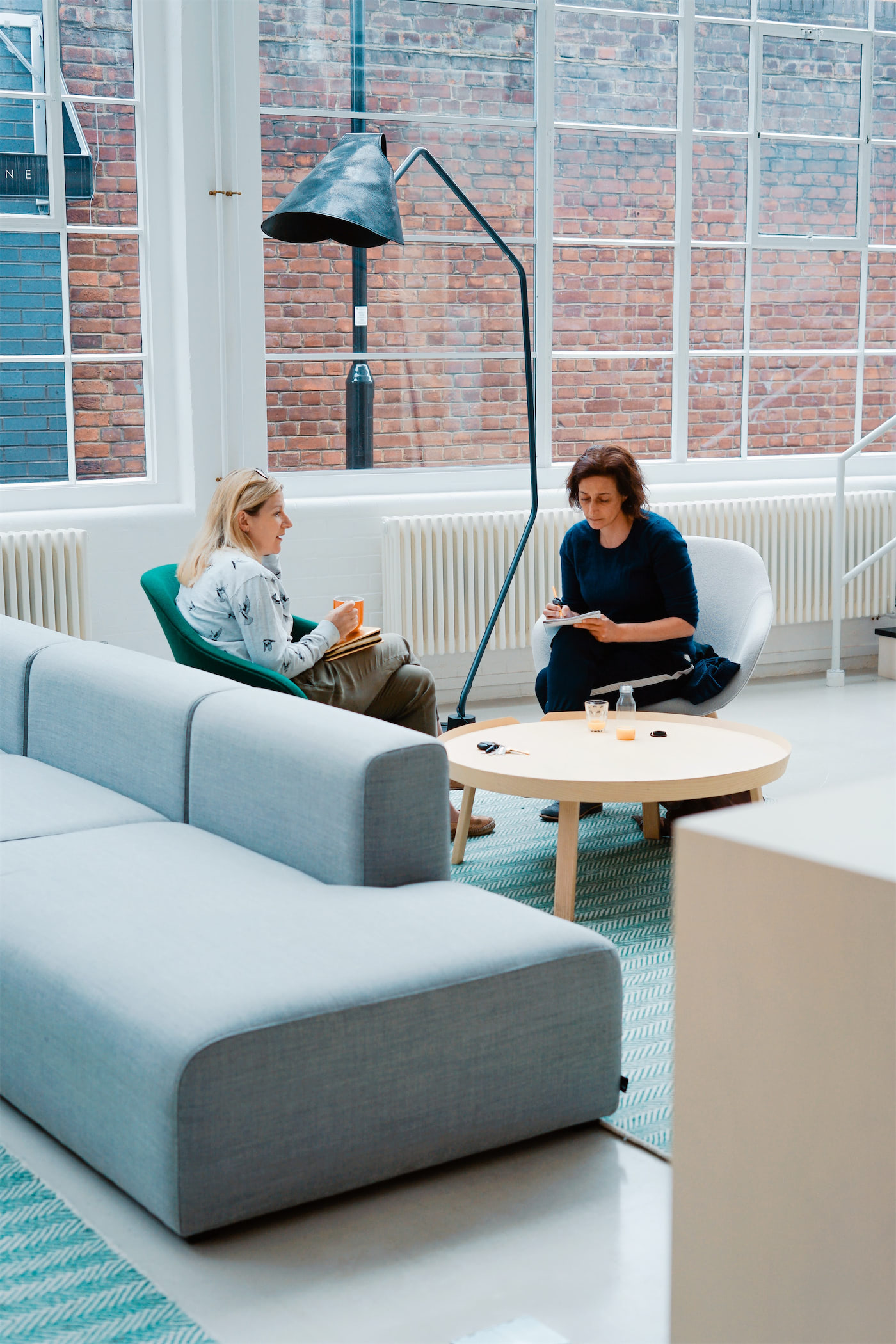 Two woman sitting and chatting in a modern looking waiting room or lobby