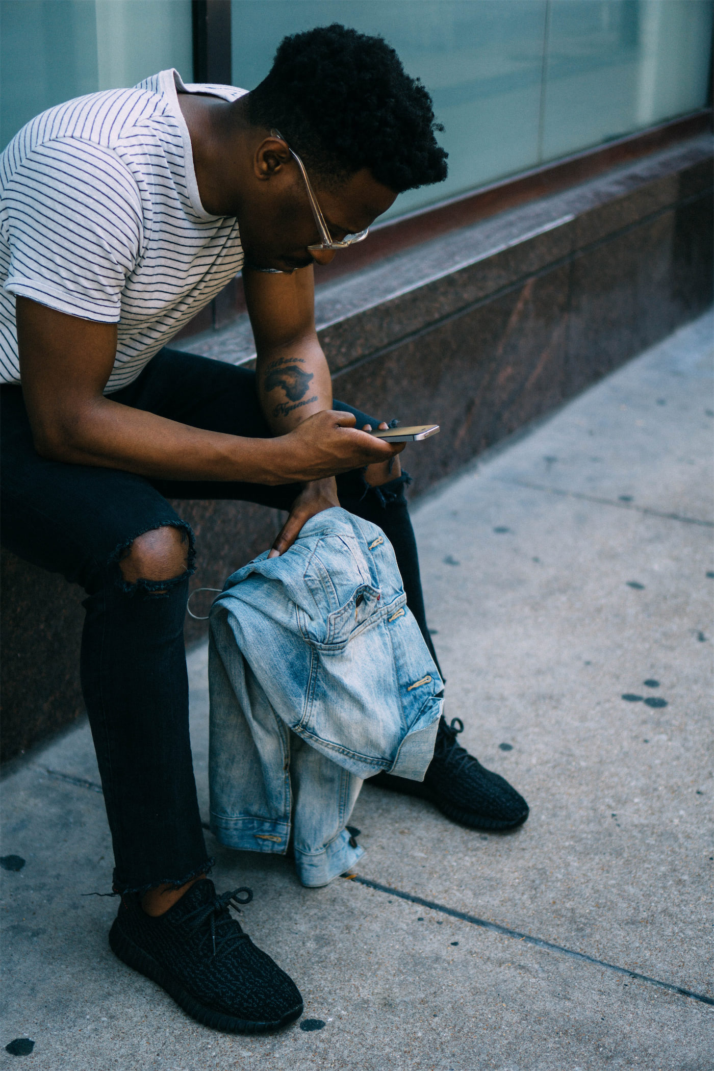 Man sitting on bench leaning forward and reading off his phone