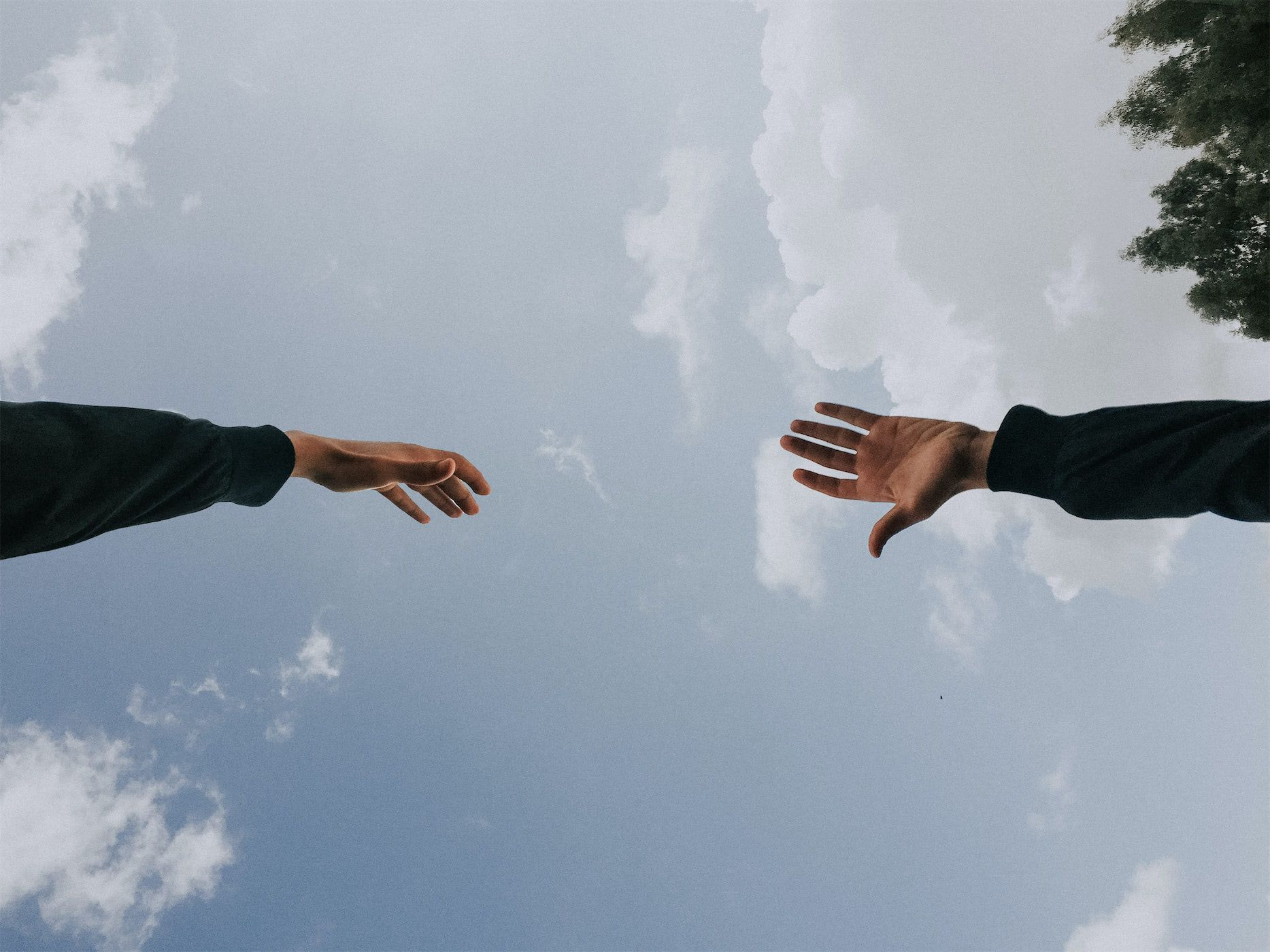 Hands reaching towards each other with a blue sky in the background