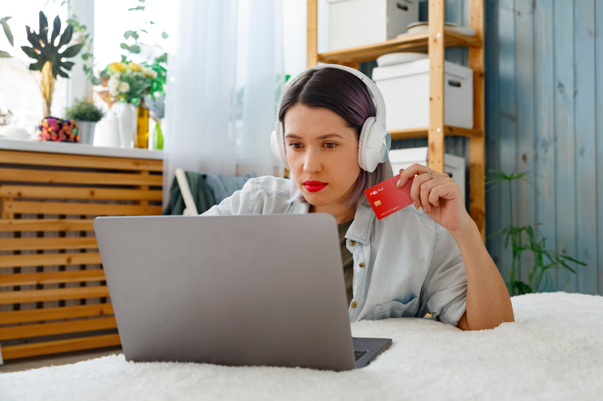 Woman holding her credit card in her hand and working on a computer