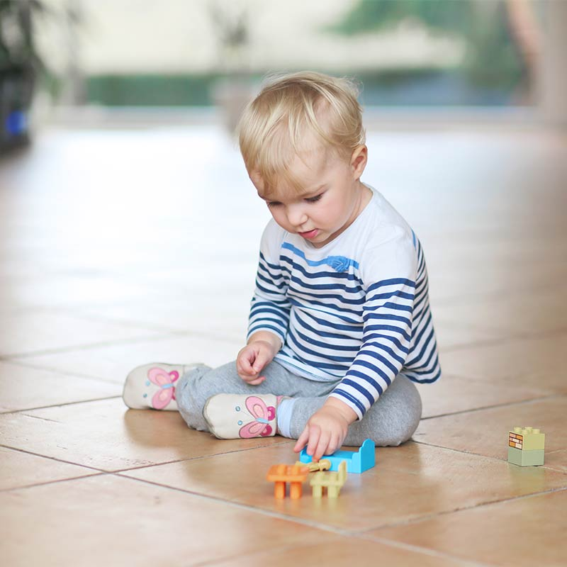 Child playing on tile floor