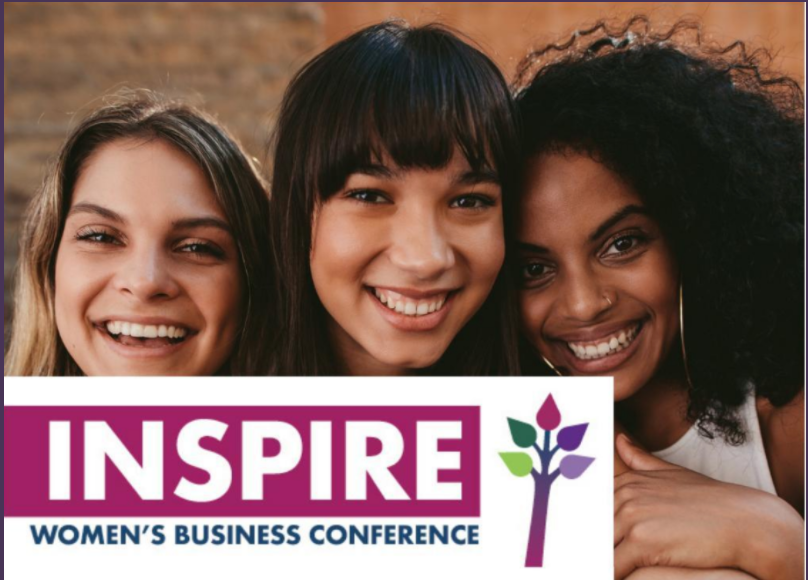 Three women smile close together with the Inspire logo superimposed in front of them