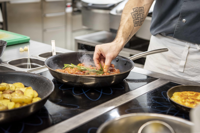 Koch kocht frisches Essen in Pfanne