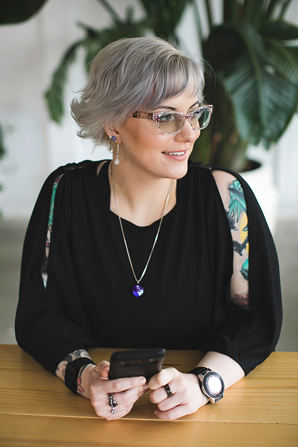 Anxiety therapist in Des Moines holds her phone while sitting at a desk.