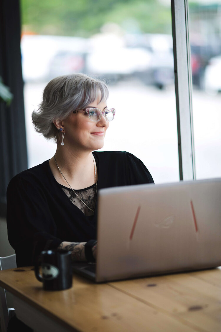 Danielle Wayne, an online anxiety therapist in Boise, replies to clients on her laptop while looking out a window.