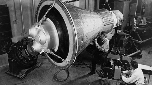 """If the heat shield was loose, Glenn's only hope of survival was that the titanium straps of the """"retropack"""" — attached, at left, to this model capsule — would hold it in place. (NASA)"""