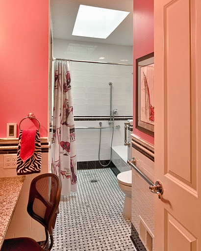 Overview of the new bathroom that consists of a roll-in shower with a tiled bench, comfort height toilet, dressing bench, and accessible vanity and sink.