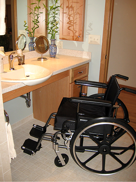Lynn's wheelchair at the new accessible sink in the bathroom.